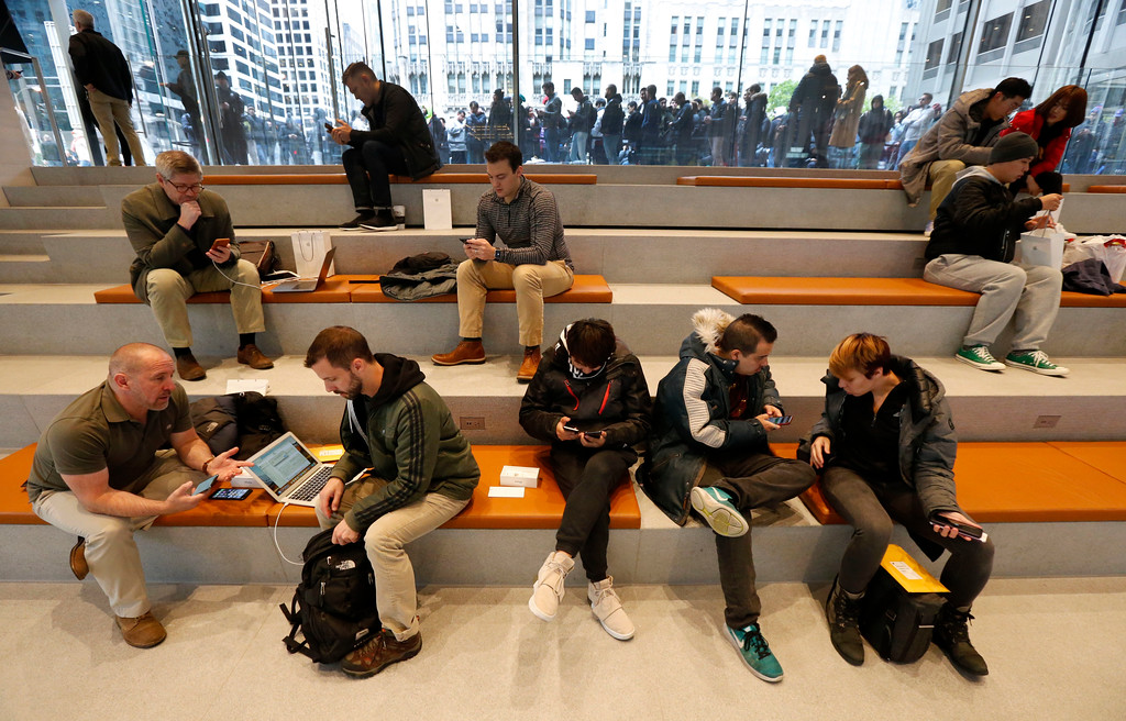 . Consumers receive assistance from Apple employees as others line up to buy the Apple iPhone X at the new Apple Michigan Avenue store along the Chicago River Friday, Nov. 3, 2017, in Chicago. (AP Photo/Charles Rex Arbogast)