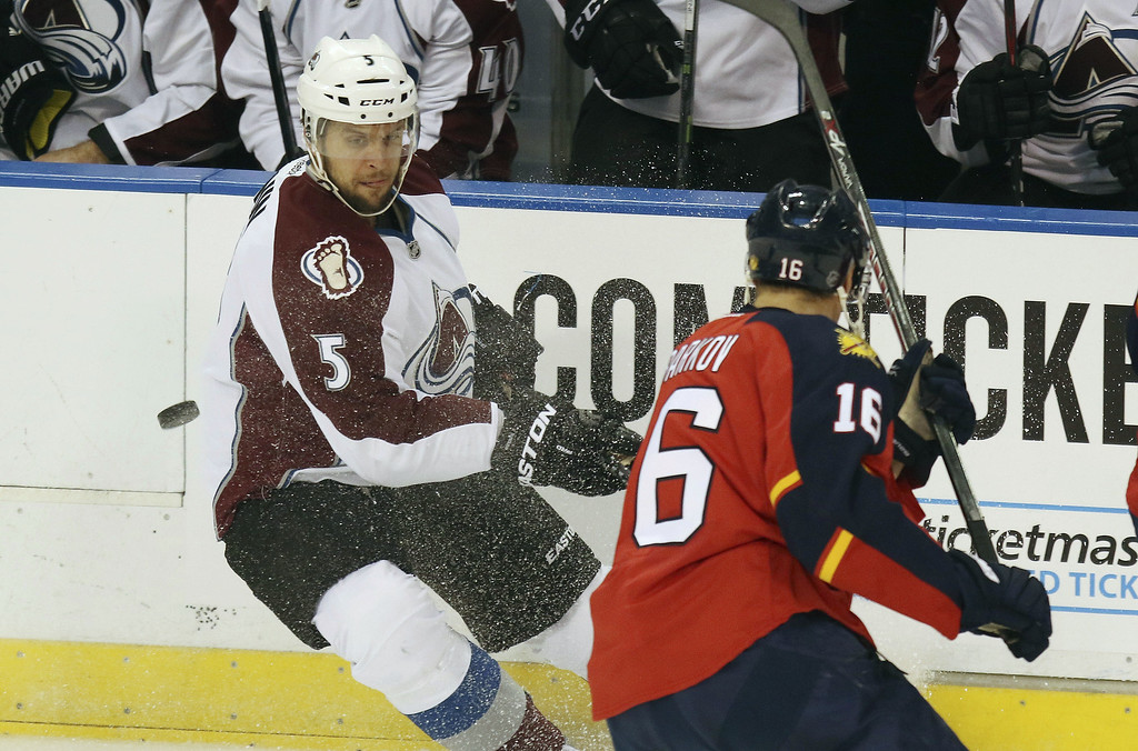 . Colorado Avalanche\'s Nate Guenin (5) and Florida Panthers\' Aleksander Barkov (16) chase a puck during the first period of an NHL hockey game, Thursday, Jan.15, 2015 in Sunrise, Fla. (AP Photo /J Pat Carter)