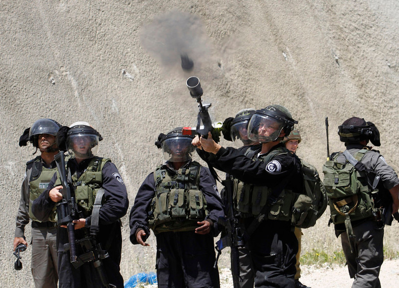 ". An Israeli border policeman fires a tear gas grenade during a Palestinian rally to commemorate the 1948 creation of the Israeli state known in Arabic as ""Nakba Day\"", or \""Day of the Catastrophe\"" outside the West Bank town of Bethlehem, Tuesday, May 14, 2013.  (AP Photo/Nasser Shiyoukhi)"