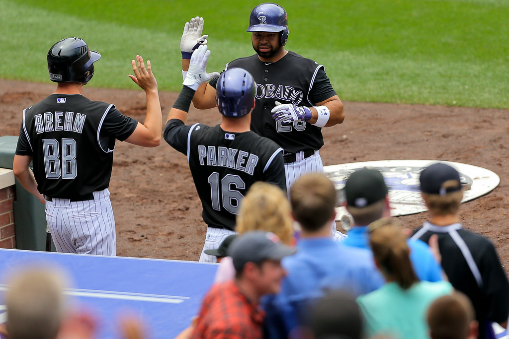 . DENVER, CO - JULY 9:  Wilin Rosario #20 of the Colorado Rockies is greeted at the dugout by Kyle Parker #16 and the bat boy after hitting a home run during the fourth inning against the San Diego Padres at Coors Field on July 9, 2014 in Denver, Colorado. (Photo by Justin Edmonds/Getty Images)
