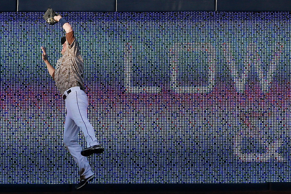 . San Diego Padres right fielder Chris Denorfia makes a leaping catch at the wall for the out on Los Angeles Dodgers\' Adrian Gonzalez during the fourth inning of an opening night baseball game on Sunday, March 30, 2014, in San Diego. (AP Photo/Gregory Bull)