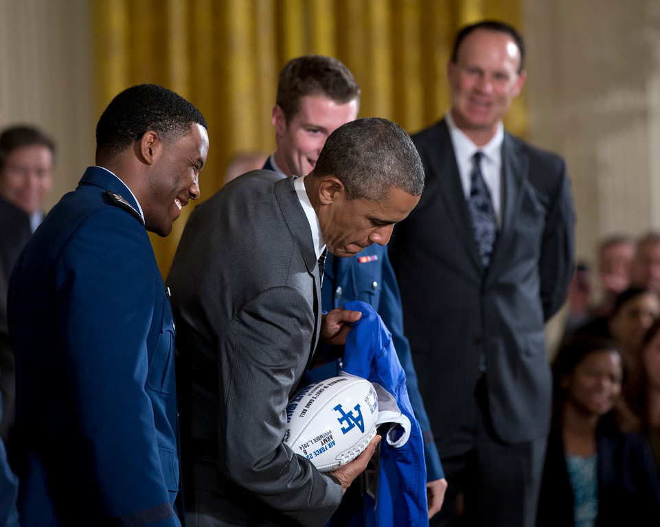 . President Barack Obama poses with a football and jersey given to him by U.S. Air Force Academy football defensive back Christian Spears, left, and quarterback Kale Pearson, third from left, an event in the East Room of the White House in Washington, Thursday, May 7, 2015. where he honored them with the Commander-in-Chief Trophy. At right is head coach Troy Calhoun. (AP Photo/Carolyn Kaster)