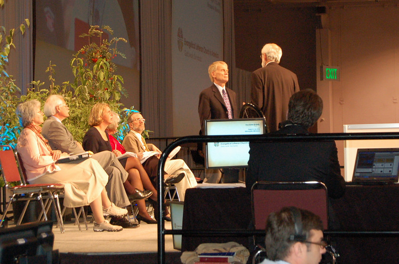 The Rev. Stan Olson, executive director, Vocation and Education, confers with Presiding Bishop Mark S. Hanson during plenary session six.