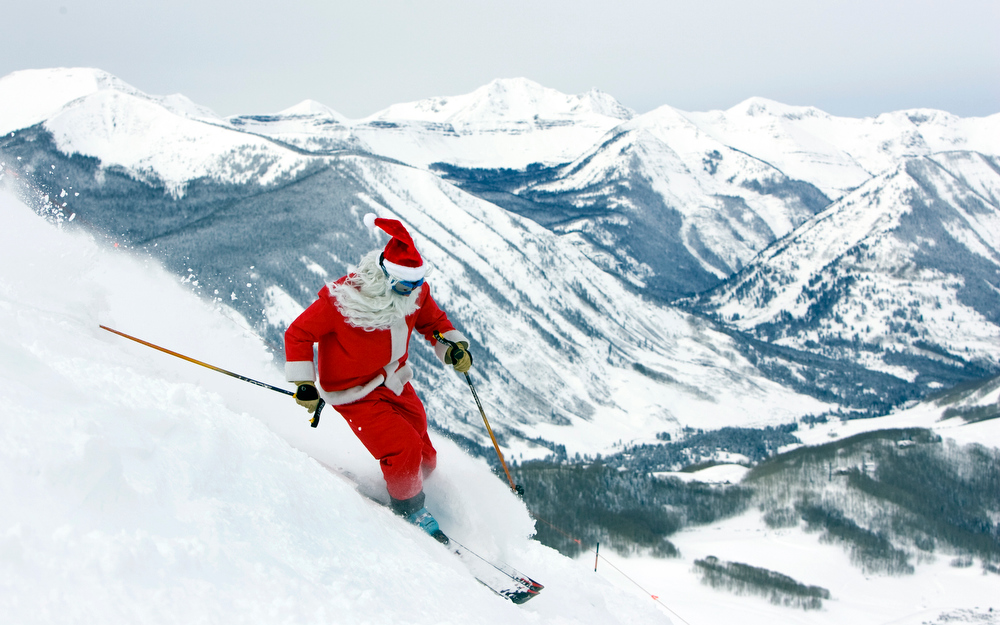 Description of . This photo provided by Crested Butte Mountain Resort shows Todd Robinson of Gunnison, Colo. dressed as Santa Claus while skiing powder snow in the Colorado Rockies at Crested Butte, Colo., the day before Christmas, Wednesday, Dec., 24, 2008. The West Elk range of the Rockies are in the background.  (AP Photo/Crested Butte Mountain Resort, Nathan Bilow)