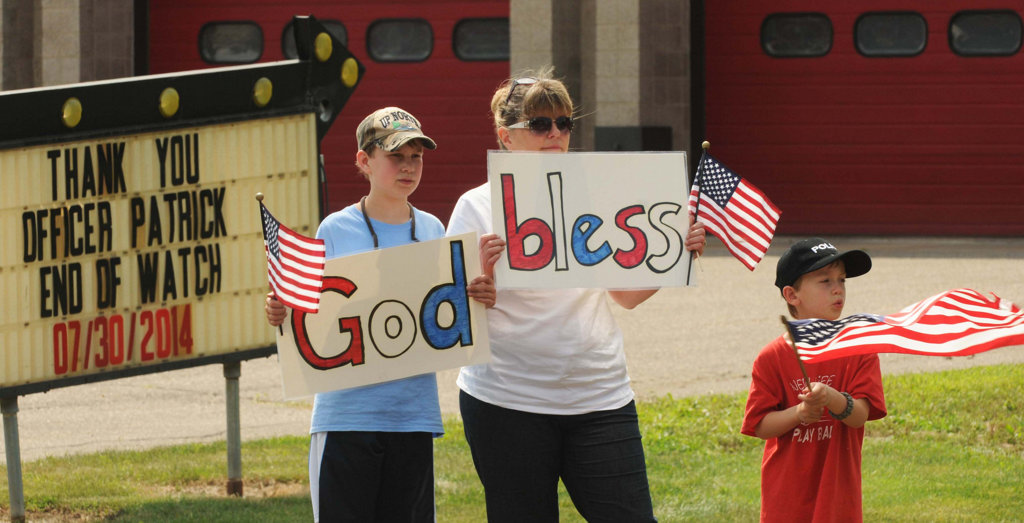 . Eleven-year-old Samuel Kayser, left, his mom Kelly and brother Matthew, 6, of Inver Grove Heights, hold signs of support near the Mendota Heights fire station. (Pioneer Press: Scott Takushi)