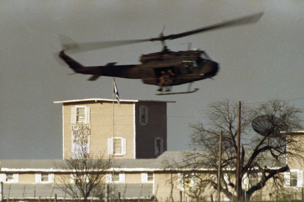". A helicopter makes a low pass over a banner that was unfurled from a window by Branch Davidian cult members at the compound near Waco, Texas on Friday, April 9, 1993. The banner reads: ""1st Seal, Rev. 6:12, PS 45, Rev. 19, PS 2, PS 18, PS 35 KJV,\"" which refers to several verses from Psalms and Revelation in the Bible. KJV refers to the King James Version of the Bible. (AP Photo/David Philip)"
