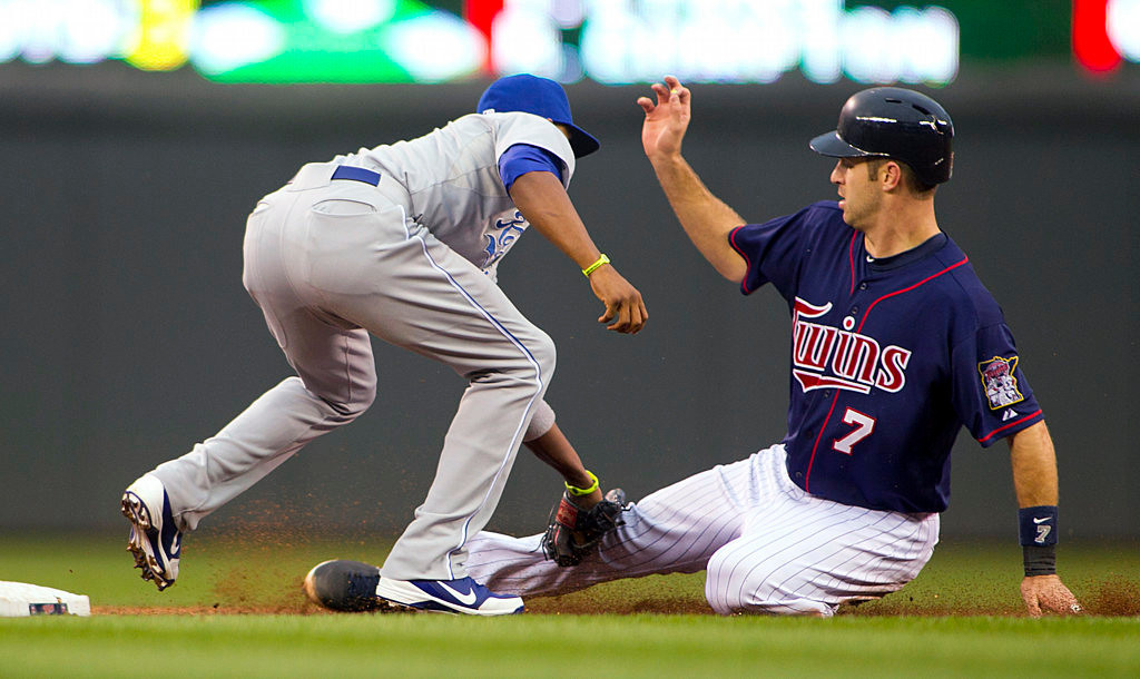 . Minnesota Twins catcher Joe Mauer (7) is tagged out on a steal attempt by Kansas City Royals shortstop Alcides Escobar in the first inning. (AP Photo/Andy King)