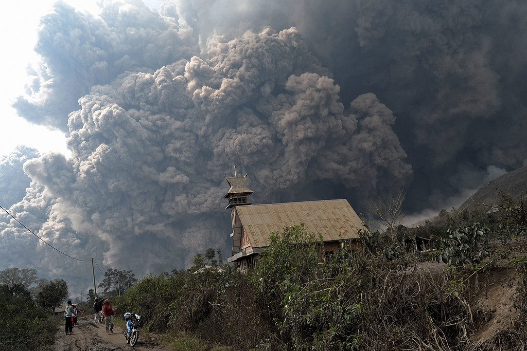 . A giant cloud of hot volcanic ash clouds engulfs villages in Karo district during the eruption of Mount Sinabung volcano located in Indonesia\'s Sumatra island on February 1, 2014. Fourteen people, including four schoolchildren, were killed February 1 after they were engulfed by scorching ash clouds spat out by Indonesia\'s Mount Sinabung in its biggest eruption in recent days, officials said.  AFP PHOTO / SUTANTA ADITYA/AFP/Getty Images