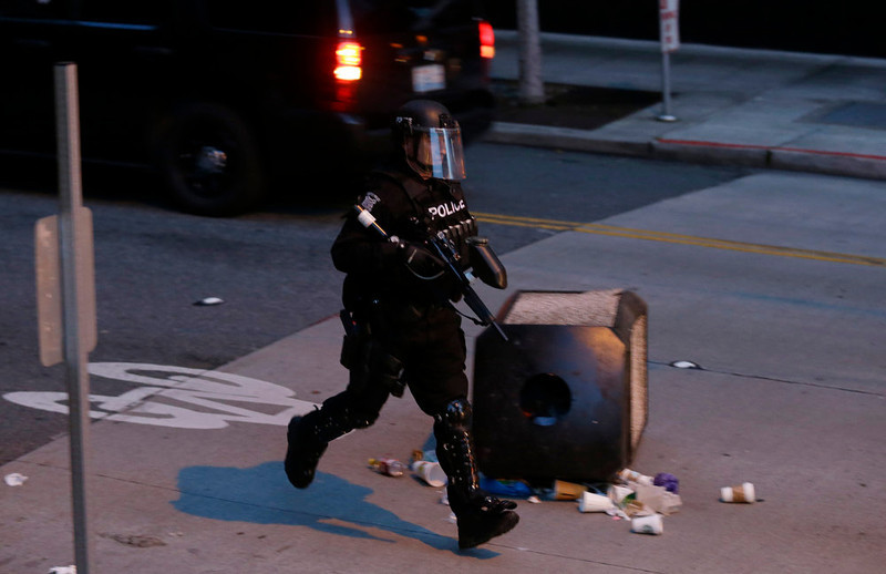 . A Seattle Police officer runs past an overturned garbage can during a May Day march that began as an anti-capitalism protest and turned into demonstrators clashing with police Wednesday, May 1, 2013, in downtown Seattle. (AP Photo/Ted S. Warren)