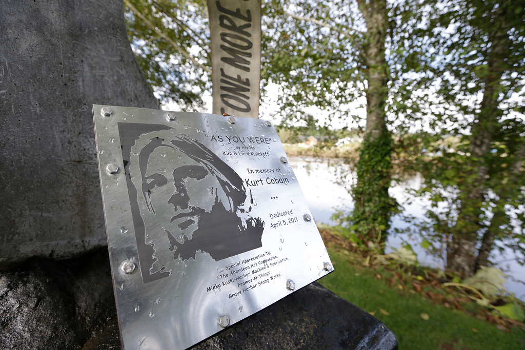 """. In this photo taken Monday, Sept. 23, 2013, a sign at \""""Kurt Cobain Landing,\"""" a tiny park blocks from the childhood home of Kurt Cobain, the late frontman of Nirvana, honors him as it overlooks the Wishkah River in Aberdeen, Wash. (AP Photo/Elaine Thompson)"""