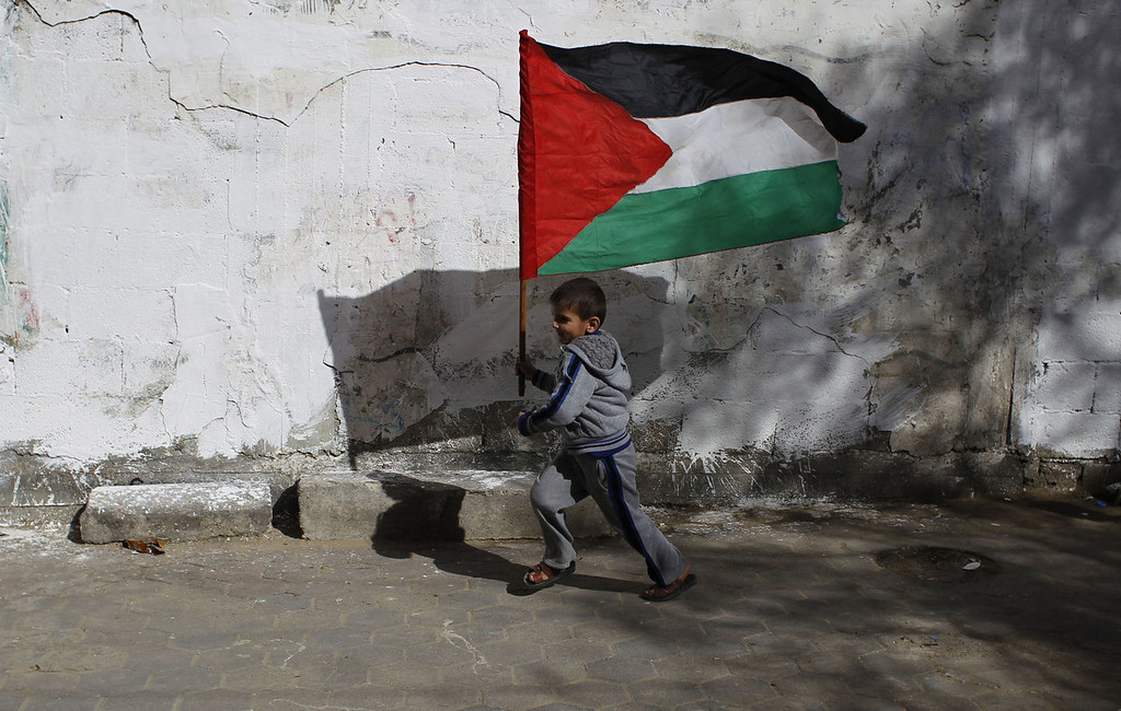 . A children runs with the Palestinian flag as friends and relatives prepare for the release of prisoner Ramy Barbakh, 37, outside his home in Khan Yunis, in the southern Gaza Strip, on December 29, 2013, after receiving the news of his impending release. Israel approved the release of 26 Palestinian prisoners, the third batch to be freed under the terms of renewed US-brokered peace talks. SAID KHATIB/AFP/Getty Images