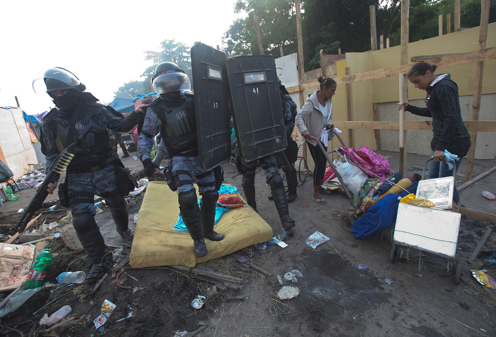 . Women carry their belongings as policemen enter to an area occupied by squatters during an eviction in Rio de Janeiro, Brazil, Friday, April 11, 2014. Squatters in Rio de Janeiro are clashing with police after a Brazilian court ordered that 5,000 people be evicted from abandoned buildings of a telecommunications company. Officers have used tear gas and stun grenades to try to disperse the families. (AP Photo/Silvia Izquierdo)