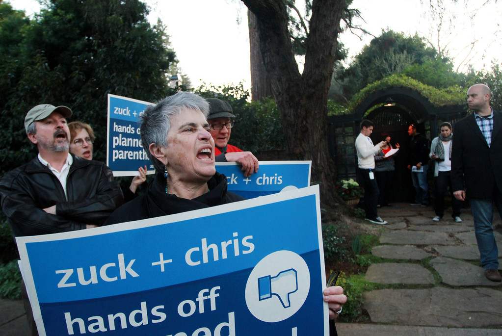 ". Barbara Slone protests in front of the house of Facebook CEO Mark Zuckerberg in Palo Alto on Wednesday, Feb. 13, 2013. About 40 protesters rallied in front of Zuckerberg�s home as the co-founder of Facebook hosted a campaign fundraiser for New Jersey Republican Gov. Chris Christie. The protesters said they objected to Christie�s visit because of his efforts to strip funding from Planned Parenthood and other women�s reproductive health care programs. Protester and Palo Alto resident Cheryl Lilienstein said she wondered whether Zuckerberg had any idea what Planned Parenthood means for women\'s health or what Christie�s stances are. ""I hope he\'s just confused,\"" she said. Zuckerberg and wife Priscilla Chan first got to know Christie after donating $100 million to struggling Newark, N.J., schools two years ago, according to a Facebook spokeswoman. (Kirstina Sangsahachart/ Daily News)"