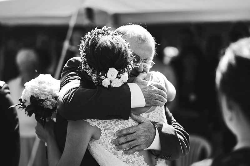 Bride and her father embrace tightly.