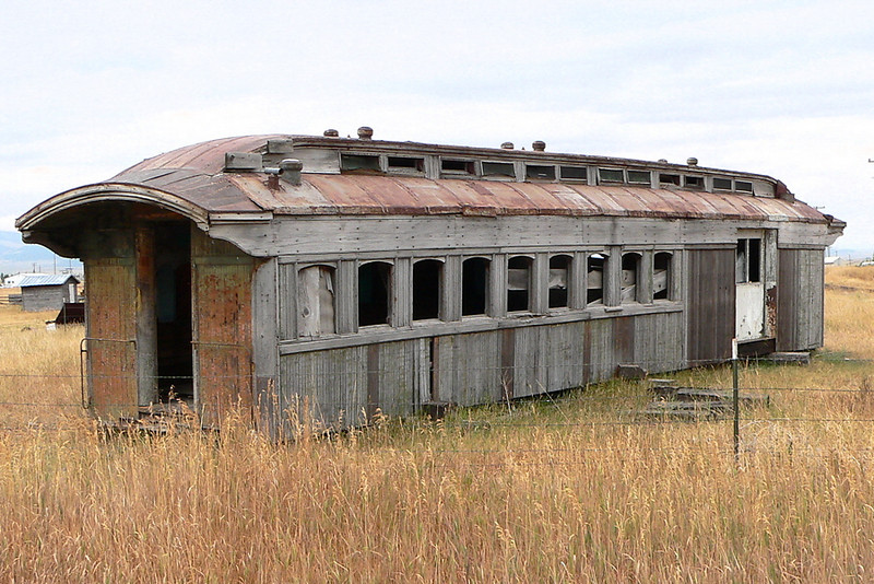 Old passenger car sitting in field at White Sulphur Springs, MT. This is an old combination car from the White Sulphur Springs and Yellowstone Park Railway which ran from WSS to Ringling, MT where it connected with the Milwaukee Road.