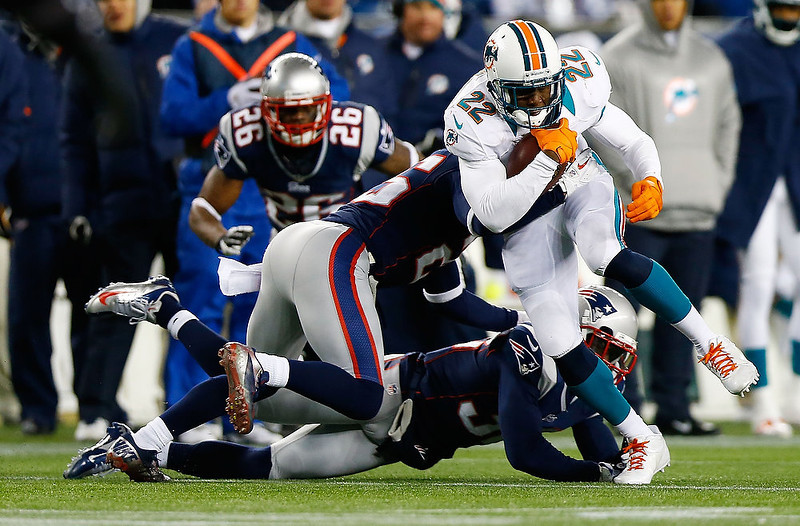 . Reggie Bush #22 of the Miami Dolphins runs with the ball around the New England Patriots defense during the game at Gillette Stadium on December 30, 2012 in Foxboro, Massachusetts. (Photo by Jared Wickerham/Getty Images)