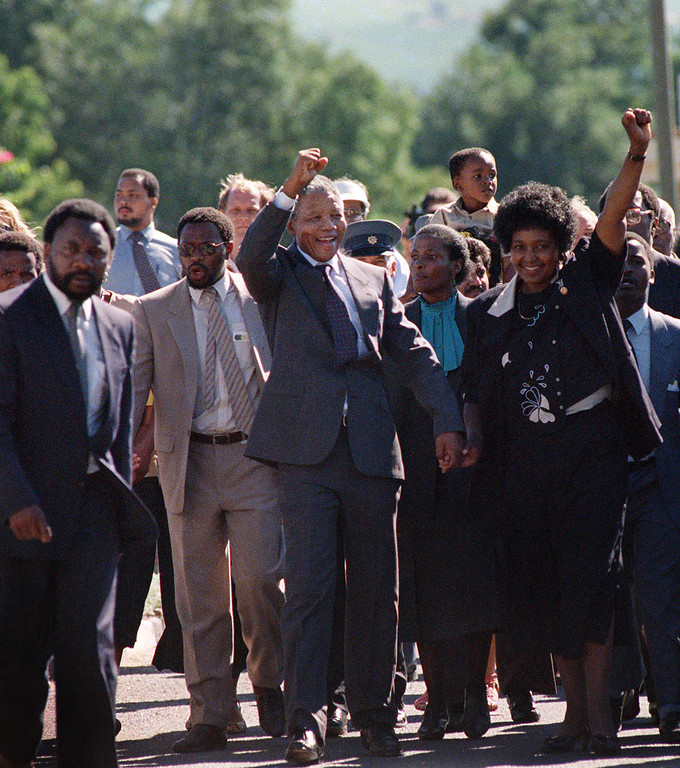 ". A picture taken on February 11, 1990 shows Nelson Mandela (C) and his then-wife Winnie raising their fists and saluting cheering crowd upon Mandela\'s release from the Victor Verster prison near Paarl. Rolihlahla Dalibhunga Mandela, affectionately known by his clan name ""Madiba\"", became commander-in-chief of Umkhonto weSizwe (Spear of the Nation), the armed underground wing of the African National Congress, in 1961, and the following year underwent military training in Algeria and Ethiopia. After more than a year underground, Mandela was captured by police and sentenced in 1964 to life in prison during the Rivonia trial, where he delivered a speech that was to become the manifesto of the anti-apartheid movement. Mandela started his prison years in the notorious Robben Island Prison, a maximum security prison on a small island 7Km off the coast near Cape Town. In April 1984 he was transferred to Pollsmoor Prison in Cape Town and in December 1988 he was moved the Victor Verster Prison near Paarl. While in prison, Mandela flatly rejected offers made by his jailers for remission of sentence in exchange for accepting the bantustan policy by recognizing the independence of the Transkei and agreeing to settle there. Again in the \'eighties Mandela rejected an offer of release on condition that he renounce violence. Prisoners cannot enter into contracts. Only free men can negotiate, he said, according to ANC reports. ( ALEXANDER JOE/AFP/Getty Images)"