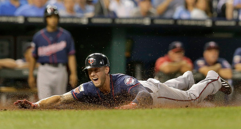 . Twins base runner Jordan Schafer slides home to score on a single by Brian Dozier during the fourth inning against the Royals. (AP Photo/Charlie Riedel)