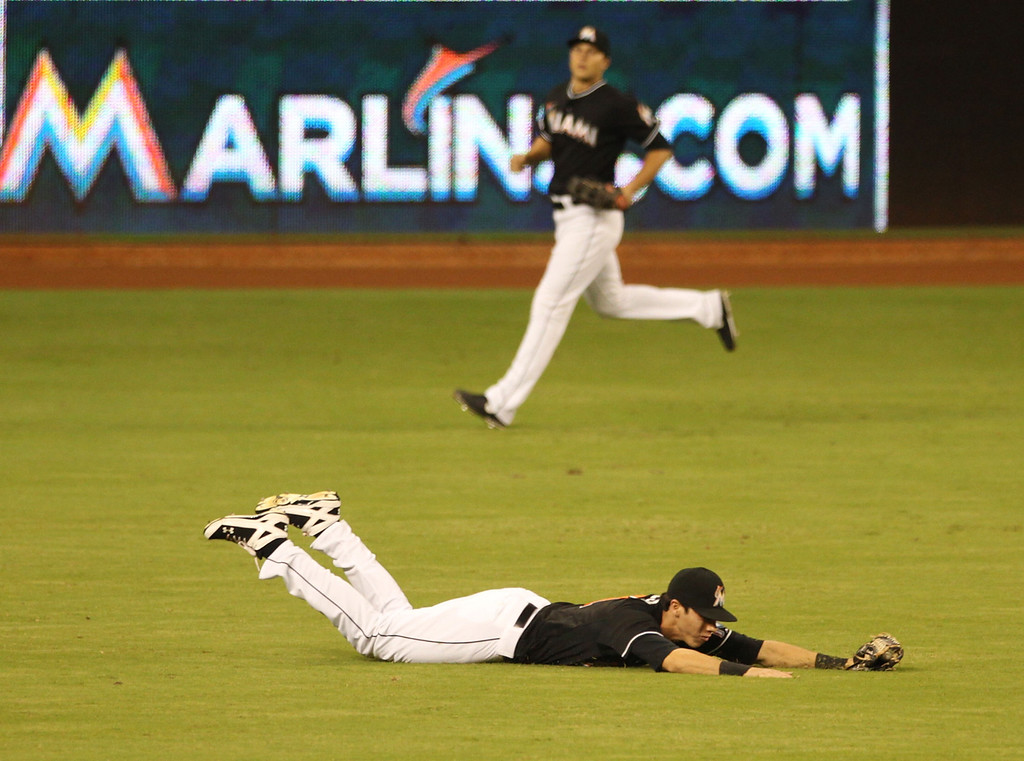 . MIAMI, FL - AUGUST 23: Outfielder Christian yelich #21 of the Miami Marlins makes a diving catch against the Colorado Rockies at Marlins Park on August 23, 2013 in Miami, Florida.  (Photo by Marc Serota/Getty Images)
