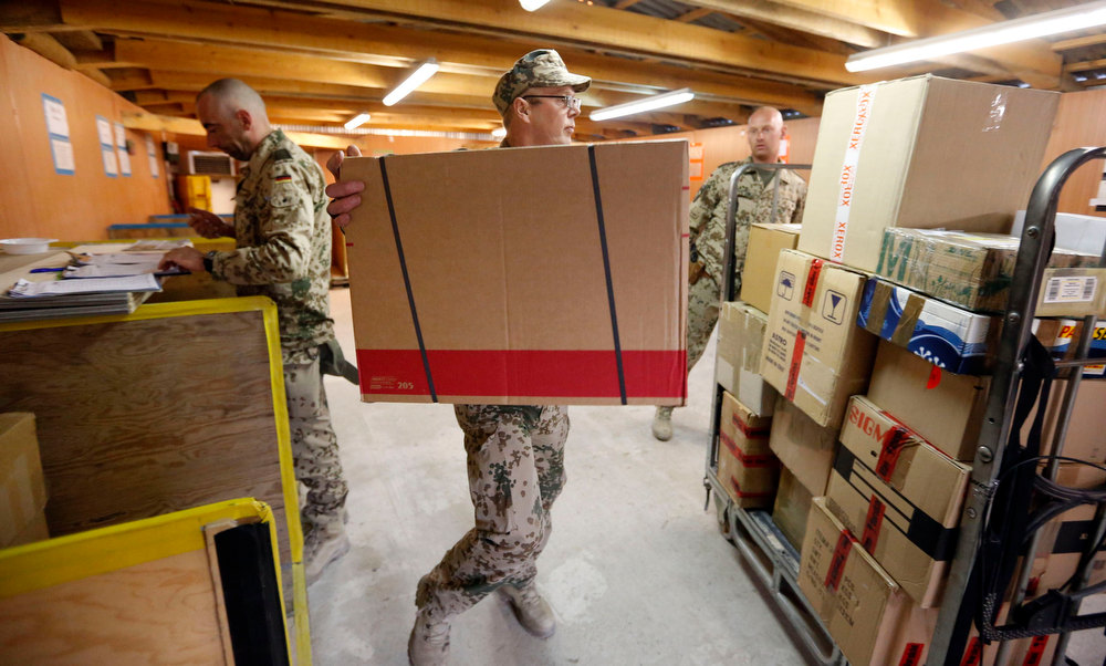 Description of . Christmas parcels are loaded by German Bundeswehr army soldiers as they arrive in an army camp in Kunduz, northern Afghanistan, December 3, 2012. REUTERS/Fabrizio Bensch