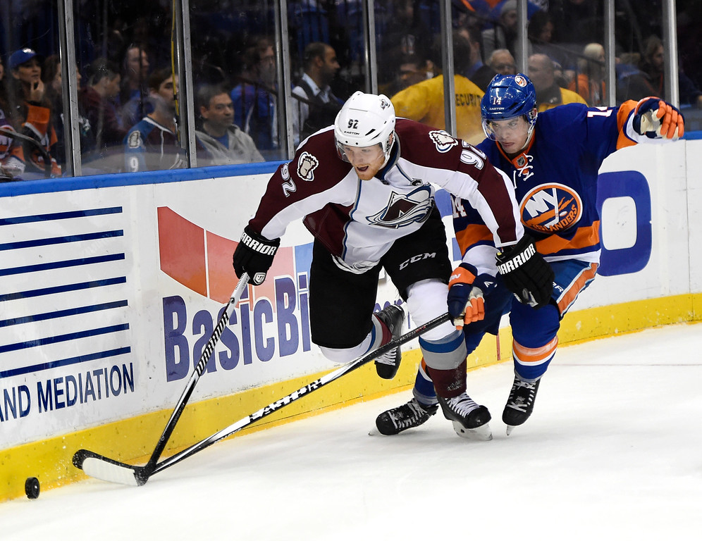 . Colorado Avalanche left wing Gabriel Landeskog (92) tries to drive the puck away from New York Islanders defenseman Thomas Hickey (14) in the first period of an NHL hockey game at Nassau Coliseum on Tuesday, Nov. 11, 2014, in Uniondale, N.Y. (AP Photo/Kathy Kmonicek)