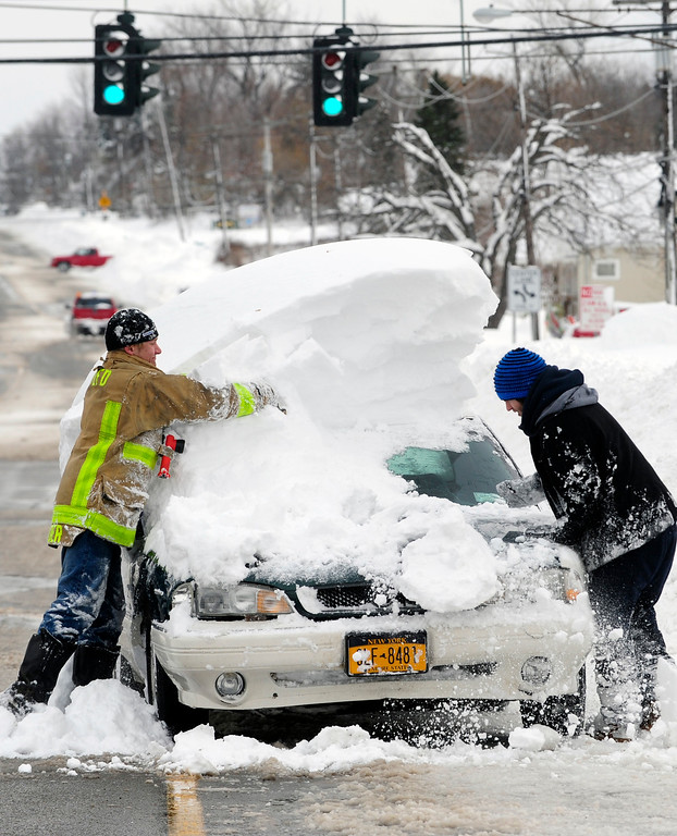 . Chris Kidder, of the Townline Fire Department assists Jacob Aronica clean a vehicle in Town Line, N.Y. Thursday, Nov. 20, 2014.  A new blast of lake-effect snow pounded Buffalo for a third day piling more misery on a city already buried by an epic, deadly snowfall that could leave some areas with nearly 8 feet of snow on the ground when it\'s all done.  (AP Photo/Gary Wiepert)