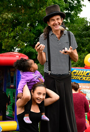9/8/2018 Mike Orazzi | Staff Geraldin Fernandez and Aaliah Steven,1, with a stilt walker during Main Street USA held in New Britain's Walnut Hill Park Saturday.