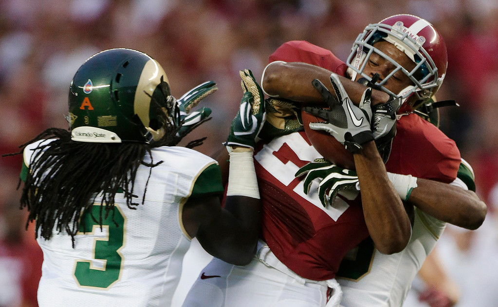 . Alabama wide receiver Christion Jones (22) is stopped by Colorado State defensive back Tyree Simmons, rear, and cornerback Shaq Bell (3) during the first half of an NCAA college football game in Tuscaloosa, Ala., Saturday, Sept. 21, 2013. (AP Photo/Dave Martin)