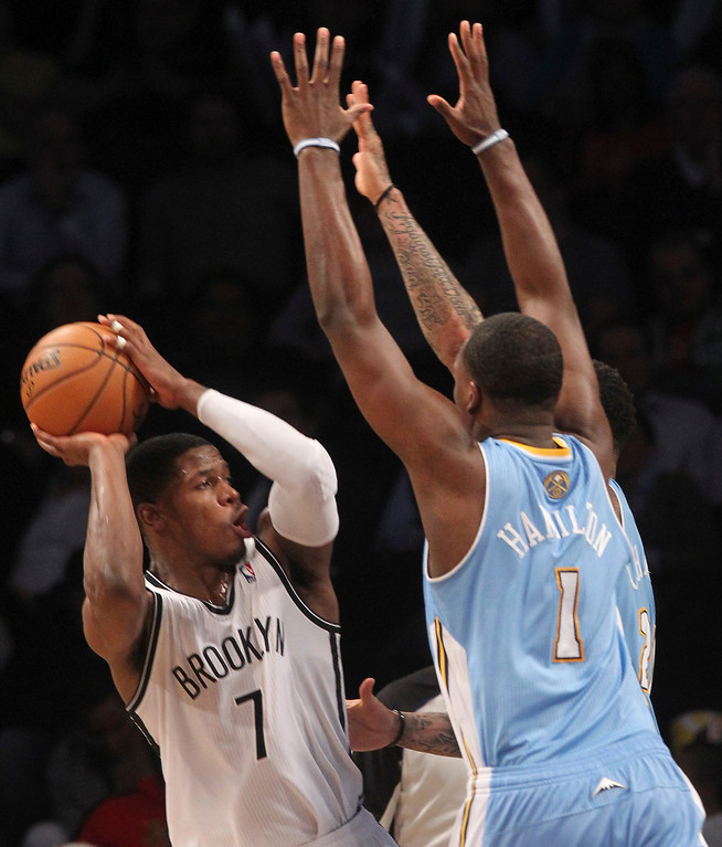 . Denver Nuggets\' Jordan Hamilton (1) blocks Brooklyn Nets\' Joe Johnson during the second half of an NBA basketball game on Wednesday, Feb. 13, 2013, at Barclays Center in New York. The Nuggets won119-108. (AP Photo/Mary Altaffer)