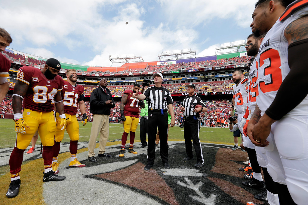. Referee Jeff Triplette tosses the coin before an NFL football game between the Washington Redskins and the Cleveland Browns, Sunday, Oct. 2, 2016, in Landover, Md. (AP Photo/Chuck Burton)