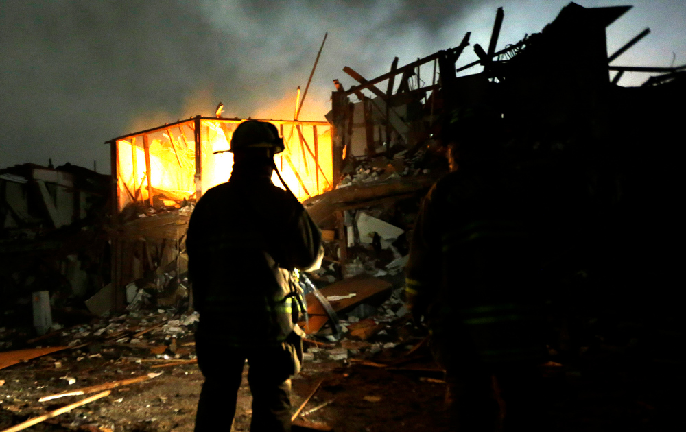 . Firefighters use flashlights to search a destroyed apartment complex near a fertilizer plant that exploded earlier in West, Texas, in this photo made early Thursday morning, April 18, 2013.  (AP Photo/LM Otero)