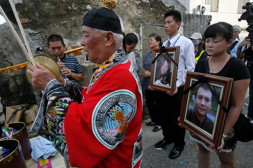 . Relatives of victims killed in the TransAsia Airways Flight GE222 crash pray with the victims\' portraits during a makeshift ceremony at the crash site on the outlying island of Penghu, Taiwan, Thursday, July 24, 2014. (AP Photo/Wally Santana)