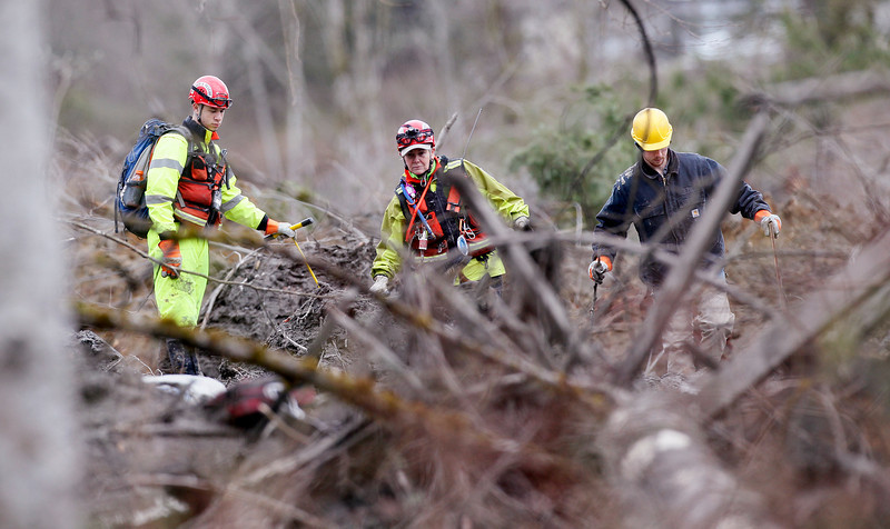. Searchers walk carefully among debris at the scene of a deadly mudslide, Wednesday, March 26, 2014, in Oso, Wash. The debris field is about a square mile and 30 to 40 feet deep in places, with a moon-like surface that includes quicksand-like muck, rain-slickened mud and ice. The terrain is difficult to navigate on foot and makes it treacherous or impossible to bring in heavy equipment. (AP Photo/Rick Wilking, Pool)