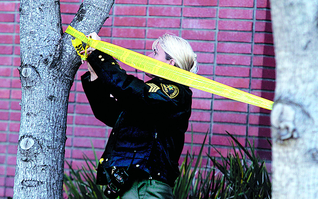. A Santa Cruz County Sheriffs Sgt. tapes off an area on a North Branciforte Avenue property on Wednesday near the spot where Jeremy Goulet allegedly murdered Santa Cruz Police detectives Elizabeth Butler and Loran \'Butch Baker on Tuesday. (Shmuel Thaler/Sentinel)