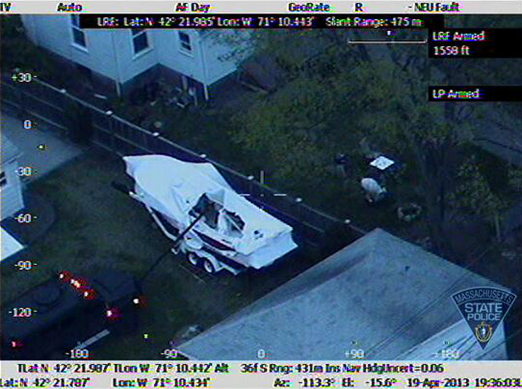 . This Friday, April 19, 2013 image made available by the Massachusetts State Police shows a police vehicle probing the boat where 19-year-old Boston Marathon bombing suspect, Dzhokhar Tsarnaev, was hiding in Watertown, Mass. He was pulled, wounded and bloody, from the boat parked in the backyard of a home in the Greater Boston area. (AP Photo/Massachusetts State Police)