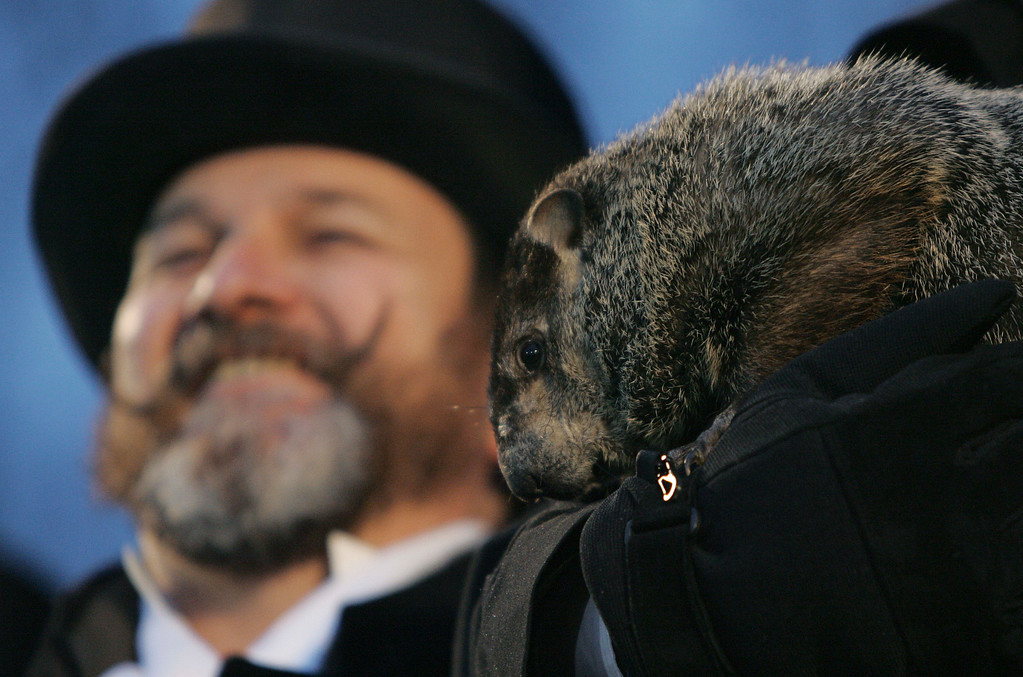 . Ben Hughes left smiles as co-handler,John Griffiths, right,  holds weather predicting groundhog Punxsutawney Phil, on Ground Hog\'s Day in Punxsutawney, Pa. on Saturday, Feb. 2, 2008. The Groundhog Club said Phil saw his shadow and predicted six more weeks of winter. (AP Photo/Keith Srakocic)