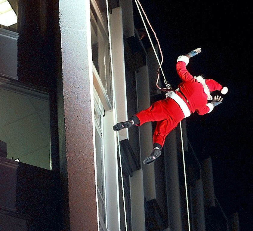 . A climber dressed as Santa Claus foregoes his normal transportation of reindeers and a sleigh and rappels down the side of the Landmark Office Building in downtown Stamford, Connecticut 11 December during a pre-Christmas event. AFP PHOTO/Timothy CLARY