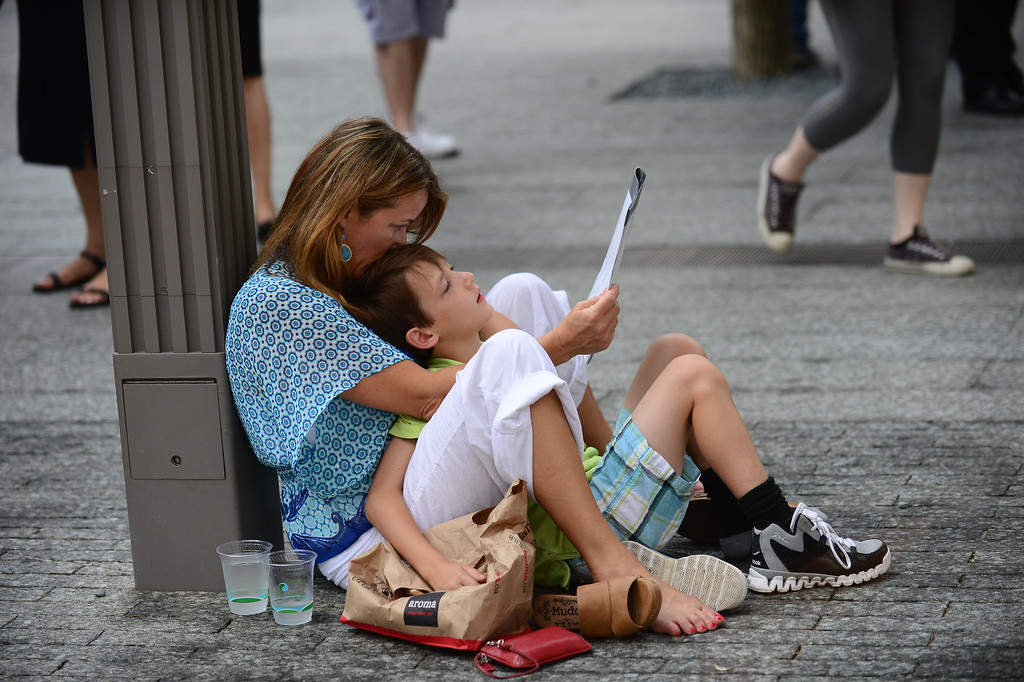 . Kara Tolmie, whose sister in law Jill Ann Metzler was among the victimes, and her son Gavin, 8, of East Setauket, New York look at a book of names of those killed during ceremonies for the twelfth anniversary of the terrorist attacks on lower Manhattan at the World Trade Center site on September 11, 2013 in New York City.  (Photo by David Handschuh-Pool/Getty Images)