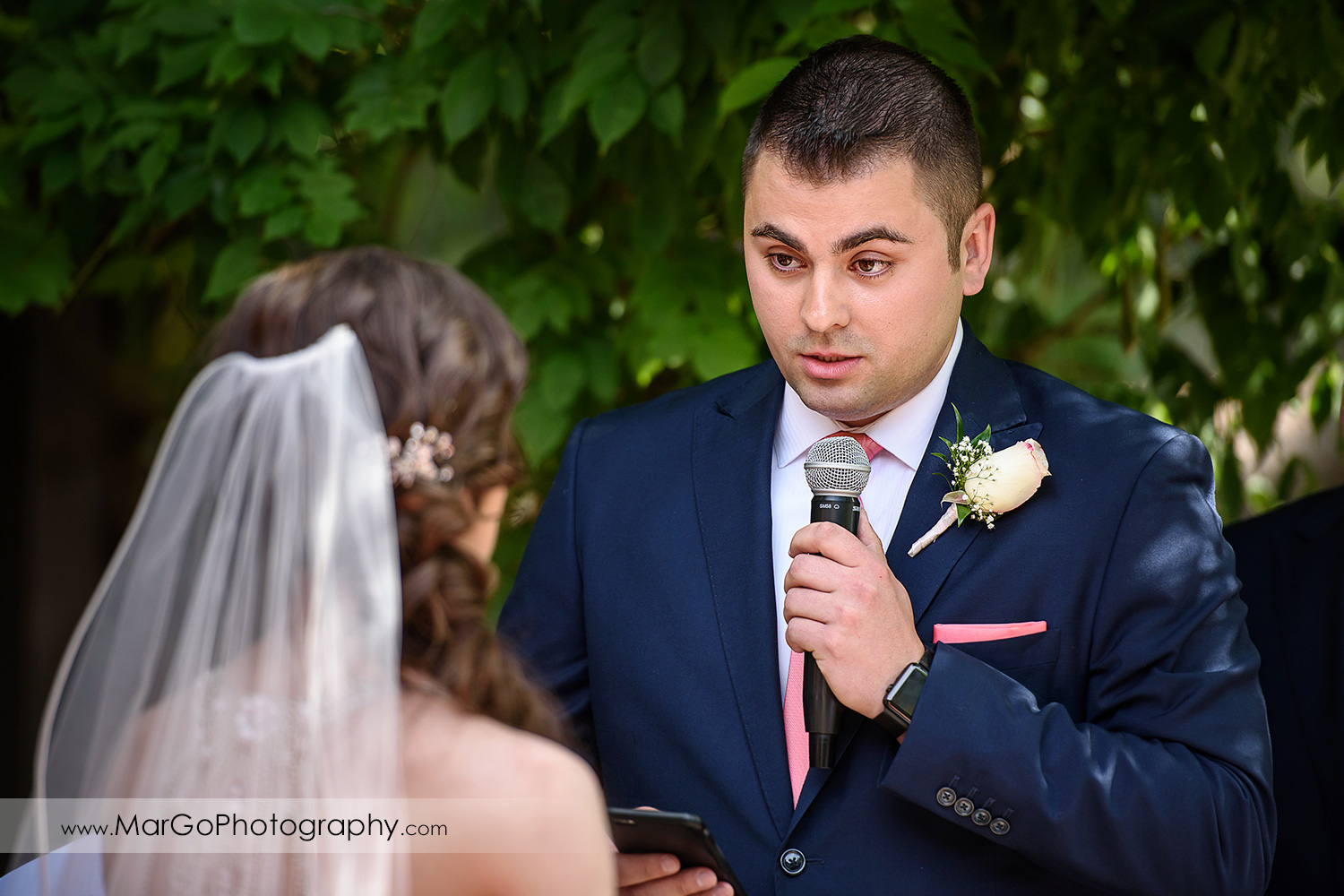 close-up of groom reading vows during wedding ceremony at Saratoga Foothill Club