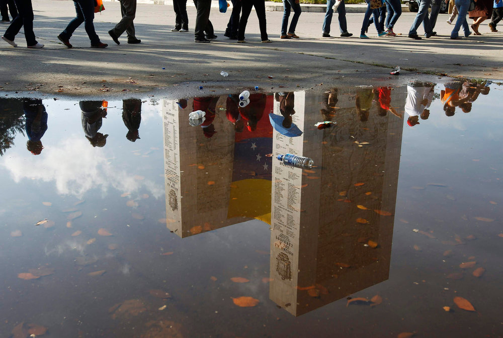 . Supporters of Venezuela\'s late President Hugo Chavez are reflected in a puddle as they line up to view his body in state, at the Military Academy in Caracas, March 7, 2013. Venezuelans flocked to pay tribute to Chavez two days after he died of cancer. The picture was rotated 180 degrees.    REUTERS/Tomas Bravo
