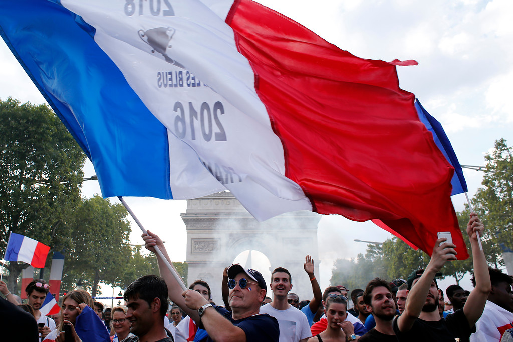 . French soccer fans react on the Champs Elysees avenue with the Arc de Triomphe on background, after defeated Croatia in the final match at the 2018 soccer World Cup, in Paris, France, Sunday, July 15, 2018. France won the final 4-2. (AP Photo/Thibault Camus)