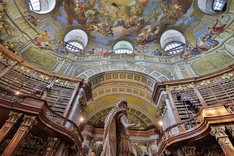 One goal of the library is to have copies of everything released in Austria for publication, including electronic media. By decree 4 copies must be presented to the Library upon release. The center statue is Emperor Karl IV, who ordered this magnificent structure built in the 1720's.