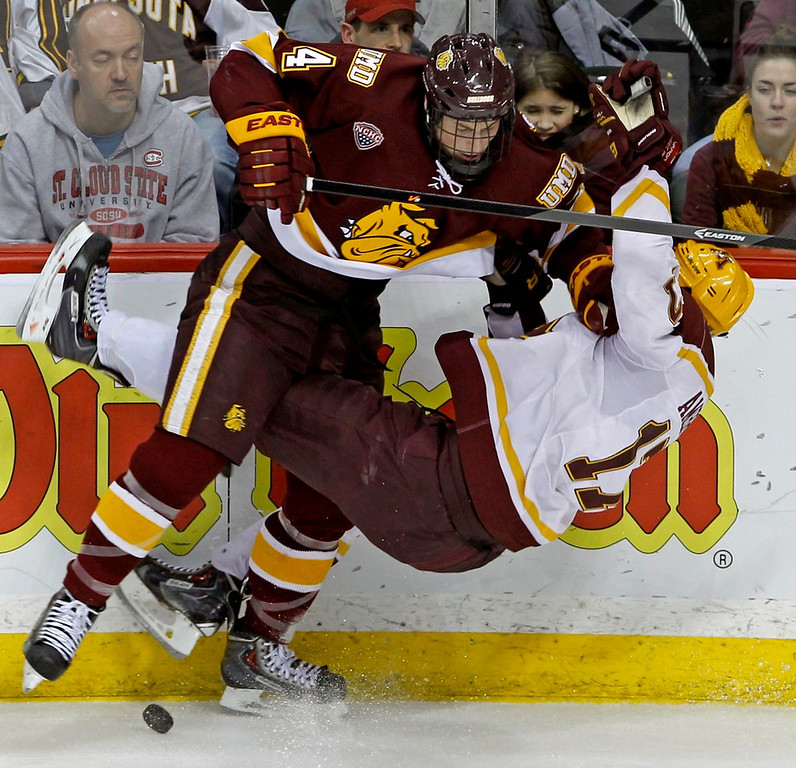 . Bulldogs defenseman Carson Soucy, left, knocks Gophers right wing Seth Ambroz off both the puck and his feet during the third period. (AP Photo/Ann Heisenfelt