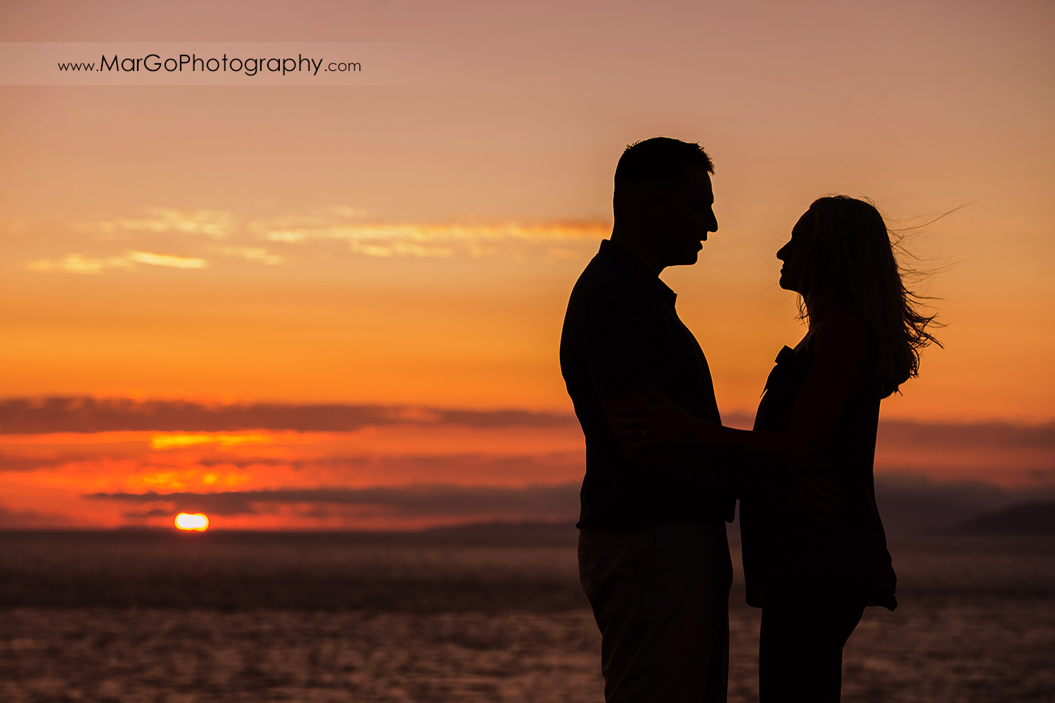 sunset silhouette of man and woman looking at each other during engagement session at San Francisco Lands End