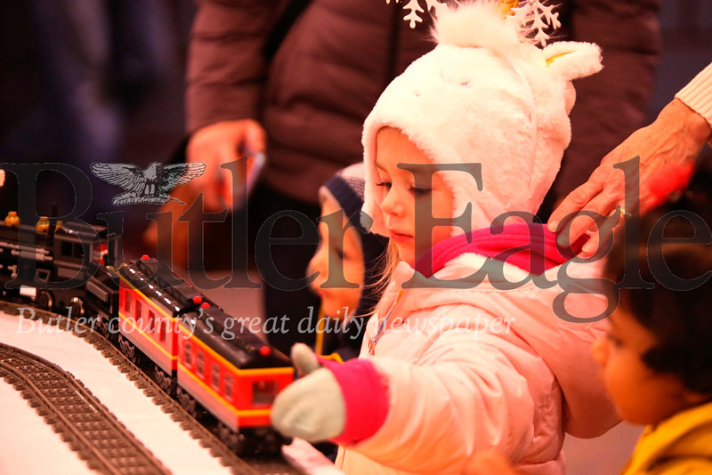 Claire Brown,3, tries to help a model train start up again at the train display at Cranberry's Santa's First Stop. Seb Foltz/Butler Eagle