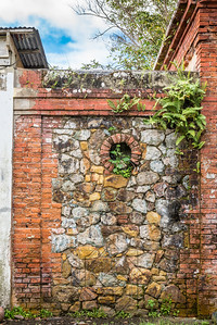 Stone and brick wall between to abandoned structures