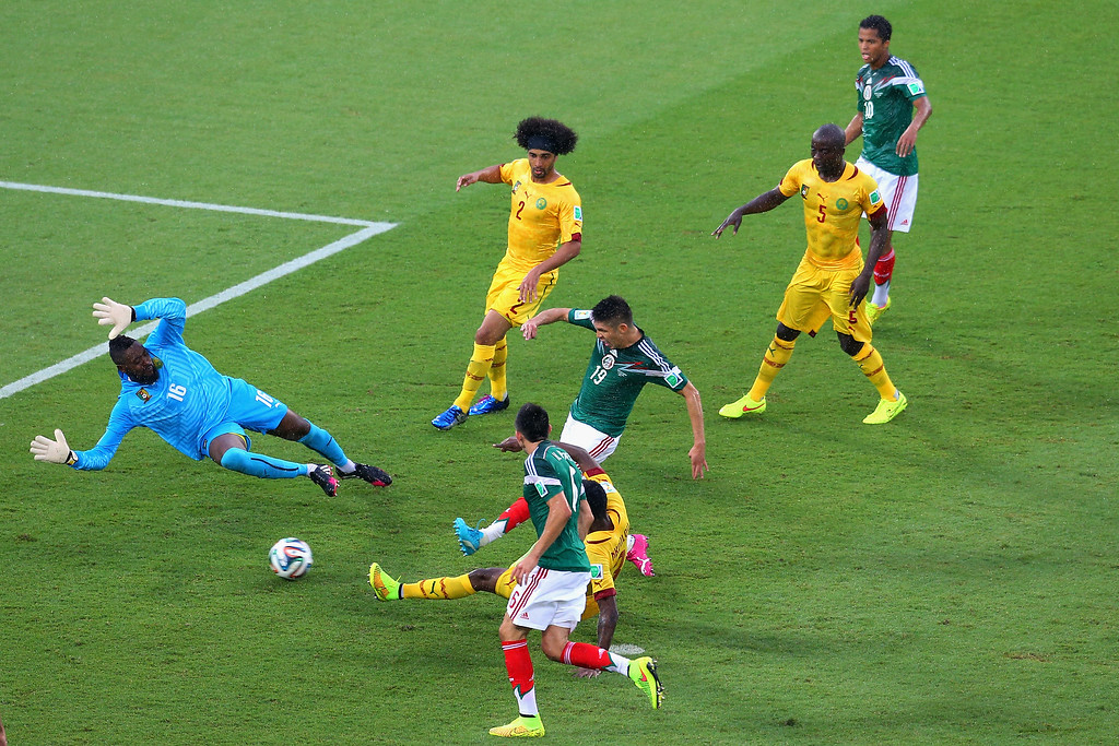 . Oribe Peralta of Mexico shoots and scores a goal past Charles Itandje of Cameroon in the second half during the 2014 FIFA World Cup Brazil Group A match between Mexico and Cameroon at Estadio das Dunas on June 13, 2014 in Natal, Brazil.  (Photo by Miguel Tovar/Getty Images)