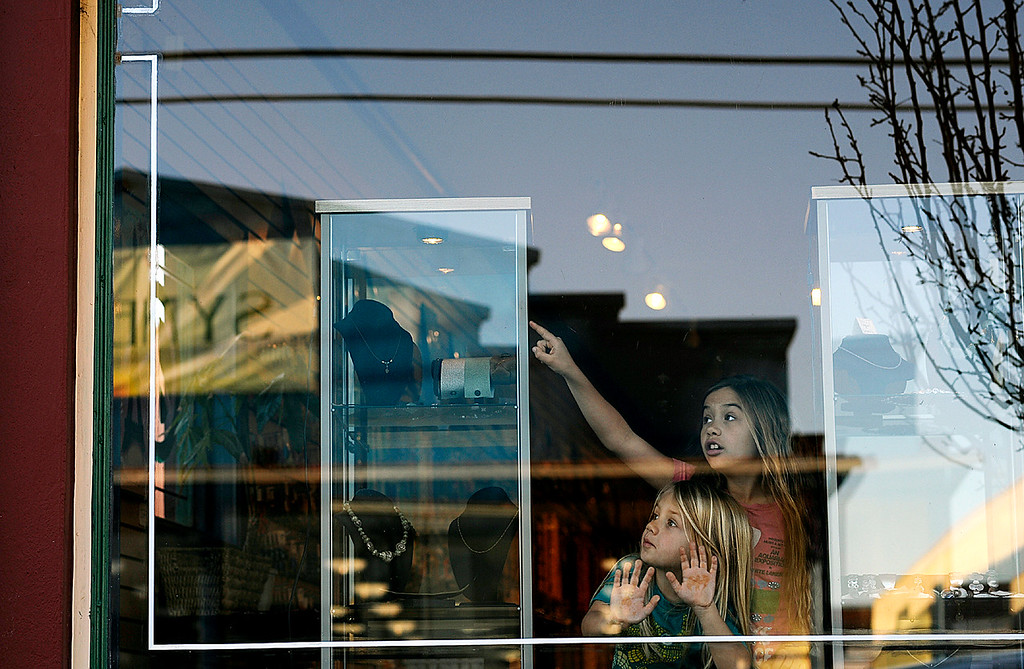 . Children inside a jewelry shop on the corner of Doyle Street watch as helicopters circle the area near Branciforte Avenue (Matthew Hintz/Sentinel)