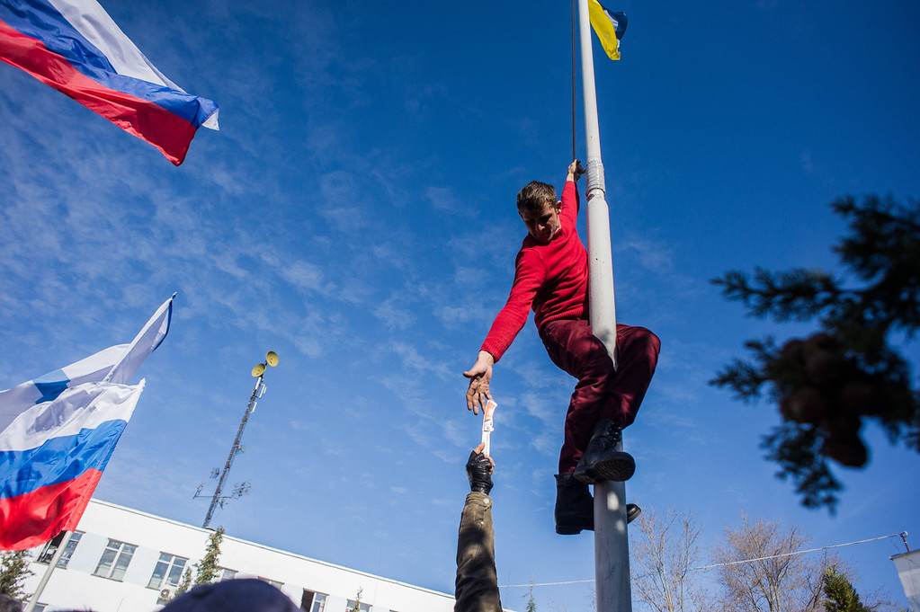 . A member of a Pro-Russian self-defense force reaches for a knife, as he takes down a Ukrainian Navy flag at the Ukrainian Navy headquarters in Sevastopol, Crimea, Wednesday, March 19, 2014.  (AP Photo/Andrew Lubimov)