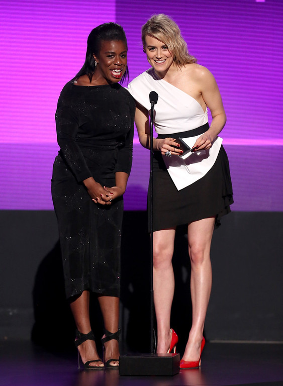. Uzo Aduba, left, and Taylor Schilling present the award for favorite pop/rock male artist on stage at the 42nd annual American Music Awards at Nokia Theatre L.A. Live on Sunday, Nov. 23, 2014, in Los Angeles. (Photo by Matt Sayles/Invision/AP)